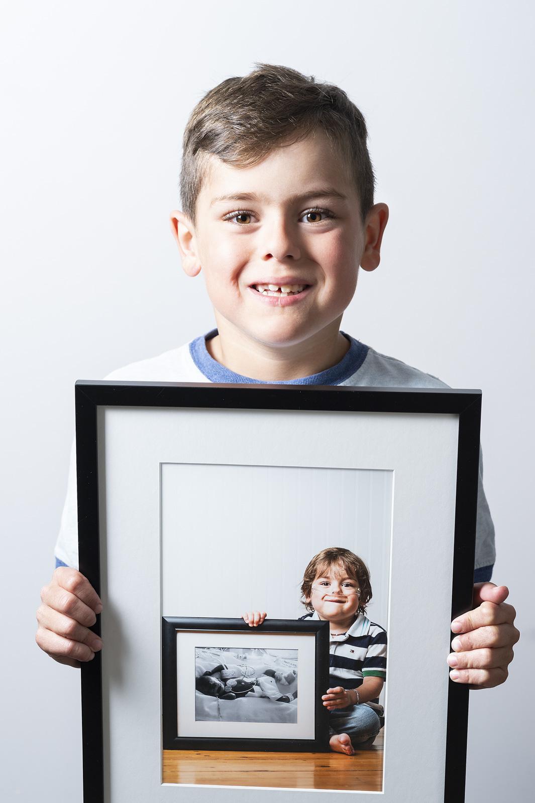 Enfant né prématurément qui tient une photo de lui plus jeune qui tient une photo de lui pendant qu'il était à l'hôpital